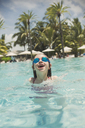 Portrait playful girl swimming with swim goggles in sunny tropical ocean - HOXF01395
