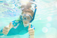 Portrait confident girl snorkeling underwater, gesturing thumbs-up - HOXF01401