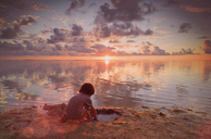 Boy playing in wet sand on tranquil sunset beach - HOXF01404