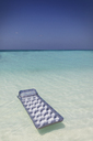 Inflatable raft floating on tranquil blue tropical ocean - HOXF01416
