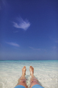 Personal perspective barefoot man laying in tropical blue ocean surf - HOXF01419