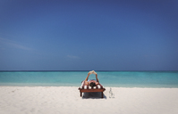 Woman relaxing, laying and reading book on lounge chair on sunny tropical beach - HOXF01425