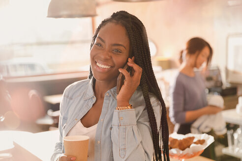 Smiling woman talking on cell phone and drinking coffee in cafe - HOXF01473