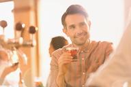 Smiling man drinking cocktail at bar - HOXF01485