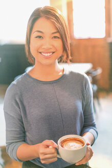 Portrait smiling Chinese woman drinking cappuccino in cafe - HOXF01506