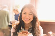 Portrait smiling Chinese woman texting with cell phone in cafe - HOXF01515