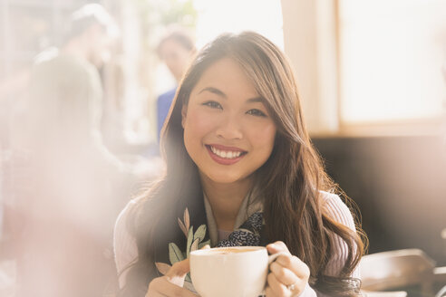 Portrait smiling Chinese woman drinking cappuccino in cafe - HOXF01524