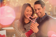 Couple holding heart-shape candy canes - HOXF01527