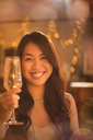 Portrait smiling Chinese woman toasting champagne flute - HOXF01536