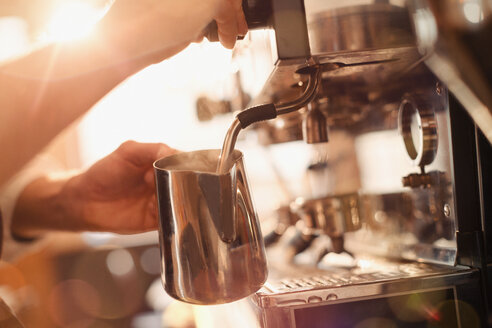 Close up barista using espresso machine milk frother - HOXF01539