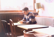 Man texting with cell phone at table in sunny cafe window - HOXF01545