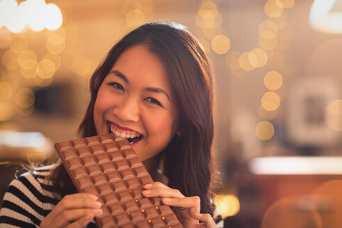 Portrait Chinese woman with sweet tooth craving biting into large chocolate bar - HOXF01566