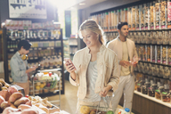 Young woman using cell phone, grocery shopping in market - HOXF01626