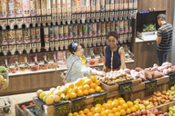 Young women grocery shopping, browsing produce in market - HOXF01635