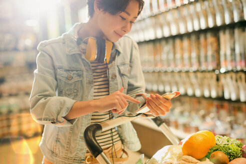 Young woman with headphones using cell phone in grocery store market - HOXF01650