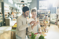 Young couple using cell phone, grocery shopping in grocery store market - HOXF01674