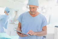 Male surgeon using digital tablet in operating room - HOXF01689