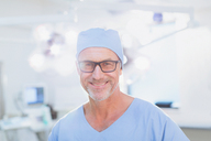 Portrait confident mature male surgeon in operating room - HOXF01695