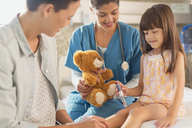 Female nurse with teddy bear watching girl patient using insulin pen in hospital room - HOXF01746