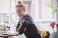 Portrait smiling young woman with headphones at laptop in cafe window - HOXF01779