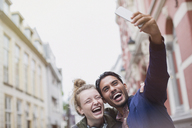Enthusiastic, laughing young couple taking selfie in city - HOXF01800