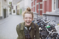 Portrait enthusiastic, laughing young woman with headphones on city street - HOXF01809