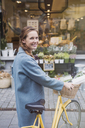 Portrait smiling woman walking bicycle at urban storefront - HOXF01815