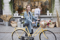 Portrait smiling woman walking bicycle with flowers in basket outside storefront - HOXF01827