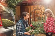 Father and daughter with Christmas wreath outside car - HOXF01866