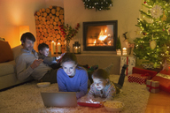 Family relaxing, using laptop, digital tablet and cell phone in ambient Christmas living room - HOXF01875