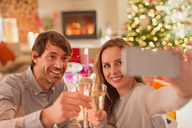 Smiling couple toasting champagne flutes and taking selfie at Christmas dinner table - HOXF01896