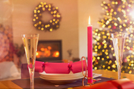 Champagne flute, candle and Christmas cracker on ambient table - HOXF01929