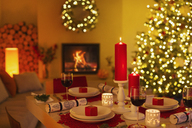 Ambient candles and Christmas crackers on dinner table in living room with fireplace and Christmas tree - HOXF01938