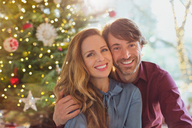 Portrait smiling couple hugging in front of Christmas tree - HOXF01941