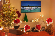 Family in Santa hats watching summer holiday video on TV in Christmas living room - HOXF01947