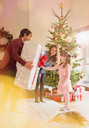 Parents giving large Christmas gift to daughter in living room next to Christmas tree - HOXF01950
