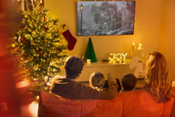 Family watching TV in Christmas living room - HOXF01953