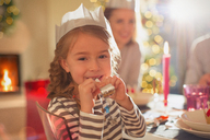 Portrait girl in Christmas paper crown holding party favor at Christmas dinner table - HOXF01956