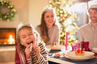 Portrait playful girl in paper crown blowing party favor at Christmas dinner table - HOXF01983