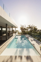 Tranquil lap swimming pool outside modern luxury home showcase exterior - HOXF01989