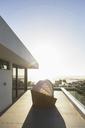 Covered patio chair on sunny modern luxury balcony under blue sky - HOXF02004