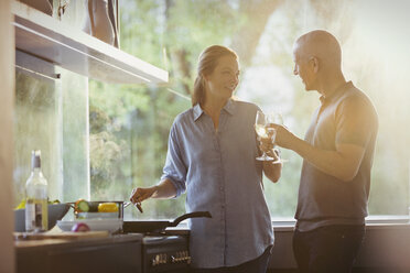 Couple toasting white wine glasses, cooking in kitchen - HOXF02007