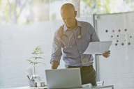 Male doctor with paperwork standing at laptop in doctor's office - HOXF02016