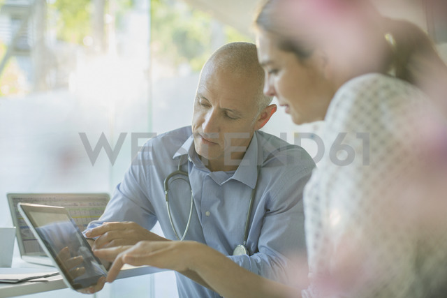 Male doctor showing digital tablet to female patient in doctor's office - HOXF02025