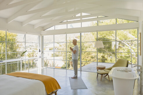 Mature man practicing yoga with hands at heart center in modern bedroom with vaulted wood beam ceilings - HOXF02049