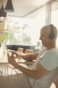 Mature man listening to music with headphones and digital tablet at dining table - HOXF02061