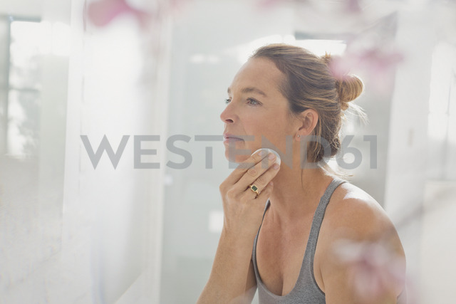 Mature woman applying makeup in bathroom mirror - HOXF02064