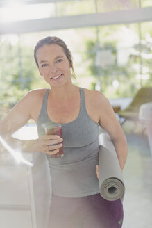 Portrait smiling mature woman with yoga mat drinking juice smoothie - HOXF02067