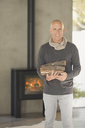 Portrait smiling mature man holding firewood in front of wood burning fireplace - HOXF02073
