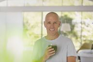 Portrait smiling mature man drinking healthy green smoothie - HOXF02076